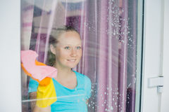 Beautiful female maid doing the housework while using a spray, washing windows Stock Image