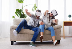 Beautiful female and male driving in VR glasses. Wide shot of beautiful female and male driving in VR glasses while sitting on sofa Royalty Free Stock Photography