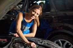 Female mechanic repairing the black car. Beautiful female mechanic smiles to the camera while repairing the black car Royalty Free Stock Image