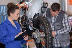 Beautiful female mechanic working on motorcycle Stock Image