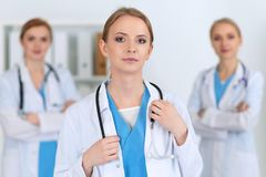 Beautiful female medical doctor standing at hospital in front of medical group. Physician is ready to help patients. Medicine and health care concept Stock Image