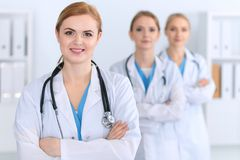 Beautiful female medical doctor standing at hospital in front of medical group. Physician is ready to help patients. Medicine and health care concept Stock Photos