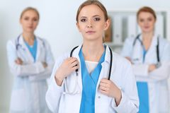 Beautiful female medical doctor standing at hospital in front of medical group. Physician is ready to help patients. Medicine and health care concept Royalty Free Stock Photography