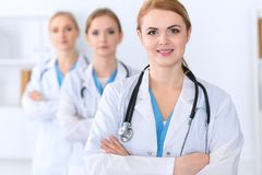 Beautiful female medical doctor standing at hospital in front of medical group. Physician is ready to help patients. Medicine and health care concept Stock Images