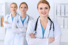 Beautiful female medical doctor standing at hospital in front of medical group. Physician is ready to help patients. Medicine and health care concept Stock Photography