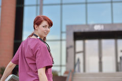 Beautiful female medical professional in scrubs outside Stock Photo