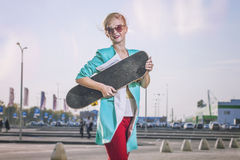 Beautiful female model in casual clothes with a skateboard. In the modern city Royalty Free Stock Image