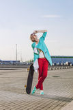 Beautiful female model in casual clothes with a skateboard Royalty Free Stock Photos