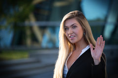Beautiful female model in the city. Beautiful female businesswoman in the city waving and looking happy Royalty Free Stock Image