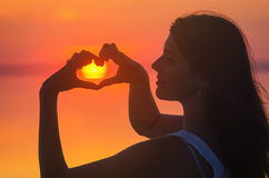 Beautiful female model enjoying sunset and making heart sign on sun. Calm water of salt lake Elton reflects woman`s silhouette. Gi Royalty Free Stock Photos
