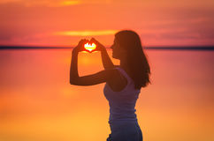 Beautiful female model enjoying sunset and making heart sign on sun. Calm water of salt lake Elton reflects woman`s silhouette. Gi Royalty Free Stock Photo