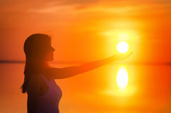 Beautiful female model enjoying sunset and touch sun at seaside. Calm water of salt lake Elton reflects woman`s silhouette. Girl i Stock Image