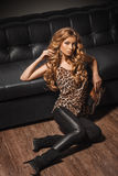 Beautiful female model at fashion with high heels sitting on the floor wearing leopard leather clothes. Stock Photography