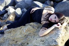 Beautiful female model laying on rocks posing Royalty Free Stock Photography