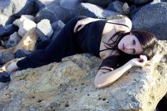 Beautiful female model laying on rocks posing Royalty Free Stock Photography