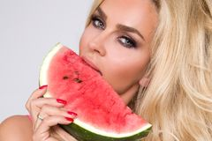Beautiful female model with long blond hair, holding a watermelon. At her face royalty free stock image