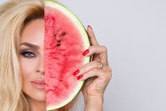 Beautiful female model with long blond hair, holding a watermelon. At her face Royalty Free Stock Images
