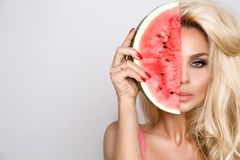 Beautiful female model with long blond hair, holding a watermelon Stock Photos