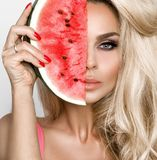 Beautiful female model with long blond hair, holding a watermelon Royalty Free Stock Photo