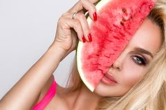 Beautiful female model with long blond hair, holding a watermelon. At her face royalty free stock photos
