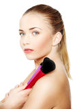 Beautiful female model with make up brushes Royalty Free Stock Images