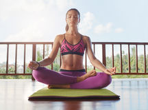 Beautiful female model meditating in lotus yoga pose. Shot of beautiful young female model meditating in lotus yoga position at health center. Healthy young Stock Photography