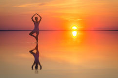 Beautiful female model open arms under sunset at seaside. Calm water of salt lake Elton reflects woman silhouette. Sun goes behind Stock Photography