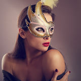 Beautiful female model posing in carnival mask with bright makeup and red lipstick on empty copy space background. Closeup. Portrait. Toned. Art royalty free stock photos