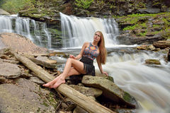 Beautiful female model posing in front of waterfall Royalty Free Stock Images