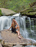 Beautiful female model posing in front of waterfall Stock Photo