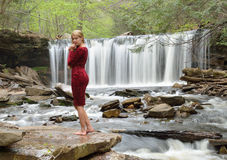 Beautiful female model posing in front of waterfall Royalty Free Stock Image