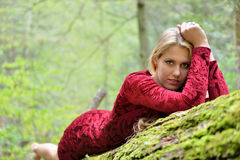 Beautiful female model posing on moss covered log Royalty Free Stock Photography
