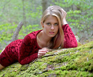 Beautiful female model posing on moss covered log Royalty Free Stock Photos