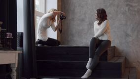 Beautiful female model posing at photo studio, photographer taking picture stock footage