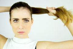 Beautiful female model pulling long hair in ponytail looking serious camera closeup Royalty Free Stock Images