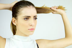 Beautiful female model pulling long hair in ponytail looking serious Stock Photo
