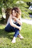Beautiful female model sitting in park. Serious woman sitting on grass waiting Royalty Free Stock Photos