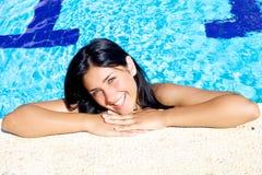 Beautiful female model smiling in swimming pool Stock Photo