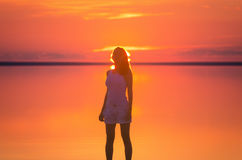 Beautiful female model stands in front of sun goes behind horizon at seaside. Salt lake Elton calm water during sunset reflects wo Stock Photos