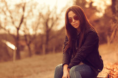 Beautiful female model at sunset. Wearing sunglasses. Outdoor po Stock Photography