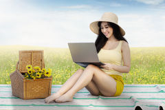 Beautiful female model uses notebook at field Royalty Free Stock Images