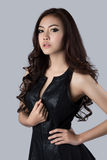 Beautiful female model wearing a leather dress. In studio Stock Photo