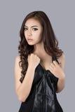 Beautiful female model wearing a leather dress. In studio Royalty Free Stock Photo
