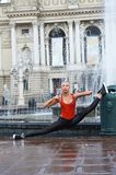 Beautiful female modern dancer performing outdoors. Gorgeous flexible female modern dancer doing splits while performing on the city street near the fountain stock photography