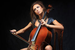 Beautiful female musician playing a cello. Stock Photos