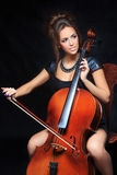 Beautiful female musician playing a cello. Stock Image
