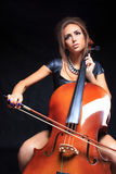 Beautiful female musician playing a cello. Stock Photo