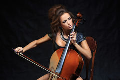 Beautiful female musician playing a cello. Stock Images