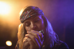 Beautiful female musician playing harmonica in nightclub Stock Image