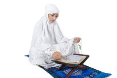 Beautiful female muslim read Kuran - isolated Stock Photos